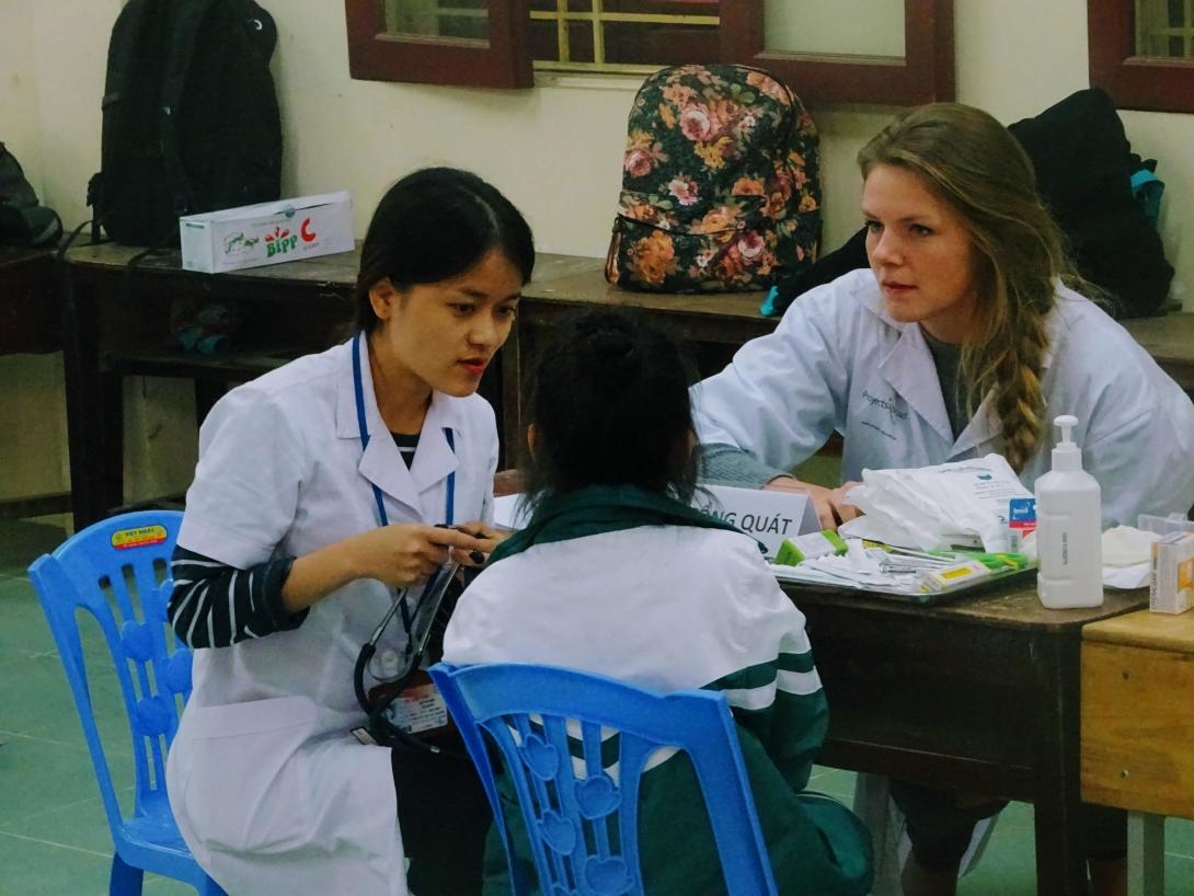 Nursing and medical elective students abroad assist at a health screening in a local Vietnamese school.